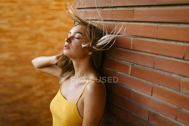 Красивая молодая женщина с взъерошенными волосами, стоящая напротив кирпичной стены на балконе — стоковое фото