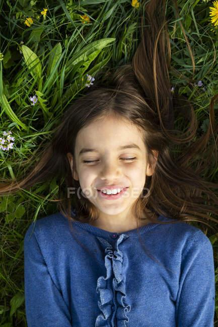 Retrato de chica con los ojos cerrados relajándose en un prado en primavera - foto de stock