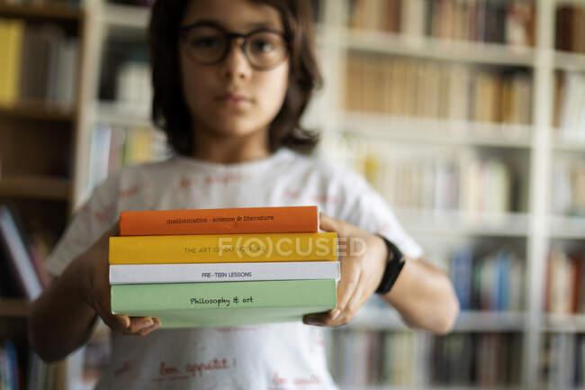 Хлопчик, що тримає чотири книжки — стокове фото