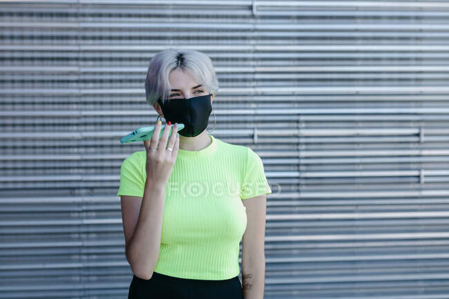 Жінка-блондинка, що стоїть перед металевим фоном, одягнена в маску обличчя за допомогою смартфона. — стокове фото