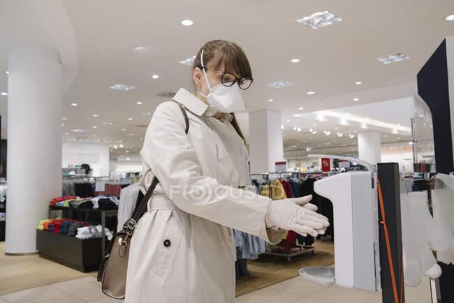 Жінка з масками обличчя і одноразовими рукавичками, які дезінфікують руки перед покупкою в магазині моди. — стокове фото