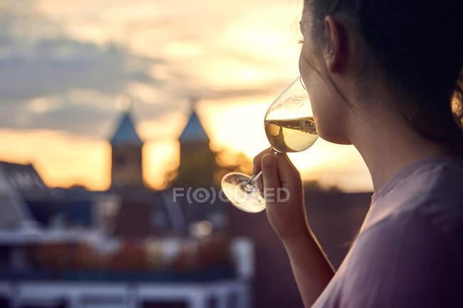 Giovane donna sul balcone bere bicchiere di vino bianco al tramonto — Foto stock