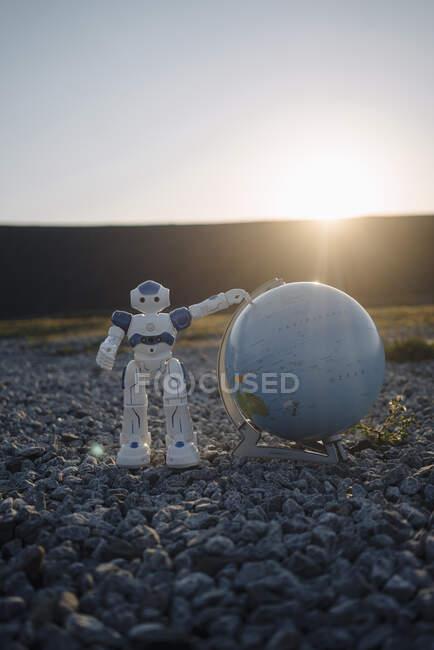 Міні - робота з глобусом на занедбаному кінці міни на заході сонця. — стокове фото