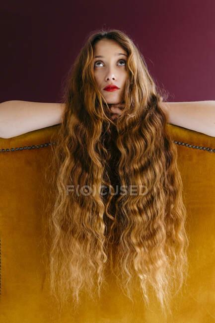 Jovem modelo de moda feminina com cabelo ondulado marrom longo encostado na cadeira dourada enquanto olha para cima contra fundo colorido — Fotografia de Stock