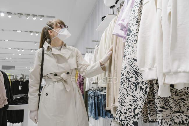 Жінка з масками обличчя та одноразовими рукавичками в магазині моди. — стокове фото