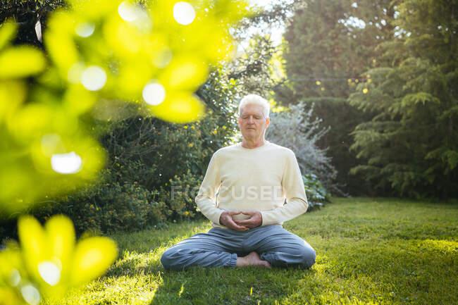 Старший медитирует в саду — стоковое фото