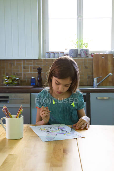 Little girl sitting at kitchen table, drawing an Easter bunny — Stock Photo