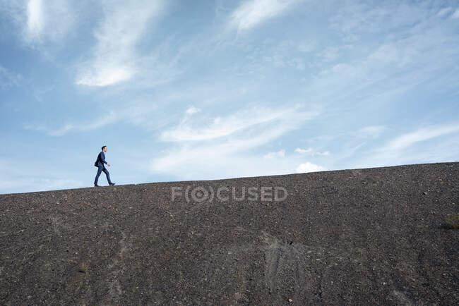 Maduro hombre de negocios caminando en una punta de mina en desuso - foto de stock