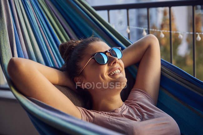Retrato de jovem feliz com óculos de sol deitado na rede na varanda — Fotografia de Stock
