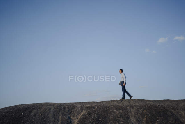 Mature businessman with laptop walking on a disused mine tip — Stock Photo