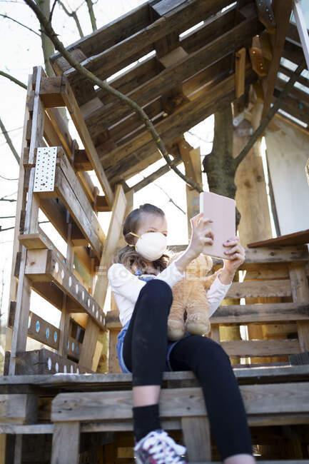 Chica con la boca máscara protectora sentado en el jardín en la casa del árbol sosteniendo una tableta y charlando a través de videollamada con sus amigos durante la cuarentena corona - foto de stock