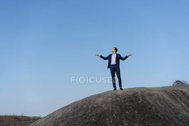 Mature businessman standing on top of a disused mine tip — Stock Photo