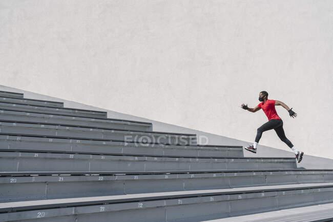 Спортсмен в маске бежит по лестнице — стоковое фото