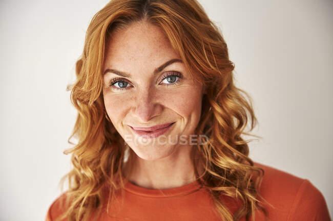 Porträt einer lächelnden rothaarigen Frau, die in die Kamera blickt — Stockfoto
