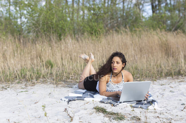Portrait of young woman lying on blanket on the beach using laptop — Stock Photo