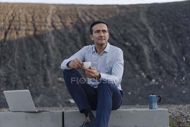 Homem de negócios maduro sentado em escadas em uma ponta de mina desutilizada ao lado de laptop ter uma pausa para o café — Fotografia de Stock