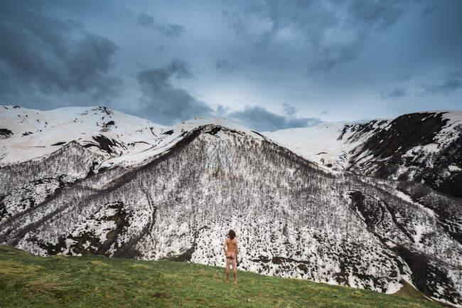 Грузія, Сванеті, Ушулі, чоловічий нудист захоплюються засніженими вершинами в горах Кавказу. — стокове фото