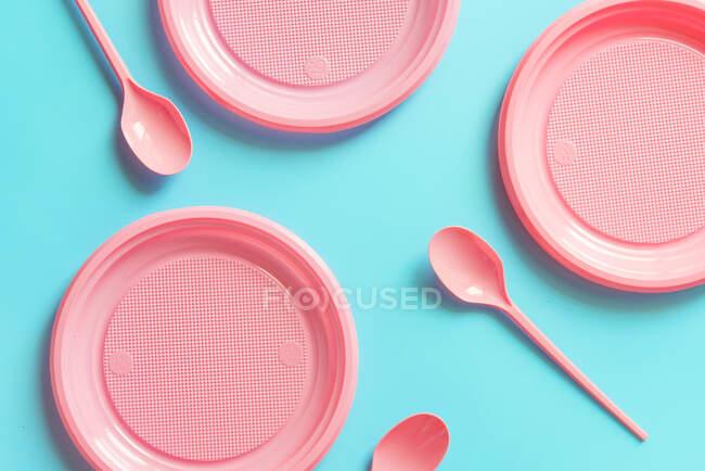 Estudio plano de platos y cucharas vacías de color rosa sobre fondo azul - foto de stock