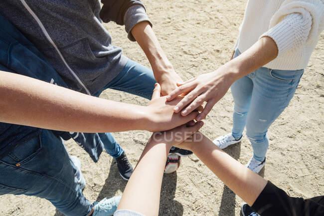 Vista de la cosecha de cinco amigos apilando sus manos - foto de stock