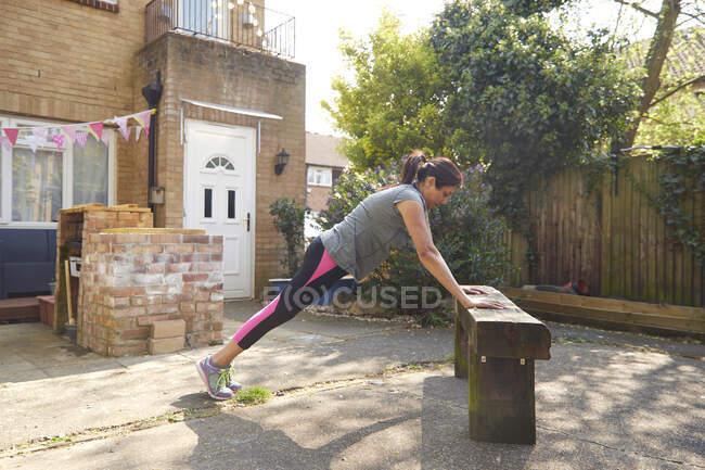 Вид сбоку женщины, делающей отжимания на деревянной скамейке на заднем дворе — стоковое фото