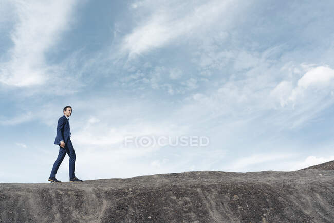 Mature businessman walking on a disused mine tip — Stock Photo
