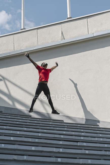 Esportista usando máscara facial pulando nas escadas — Fotografia de Stock