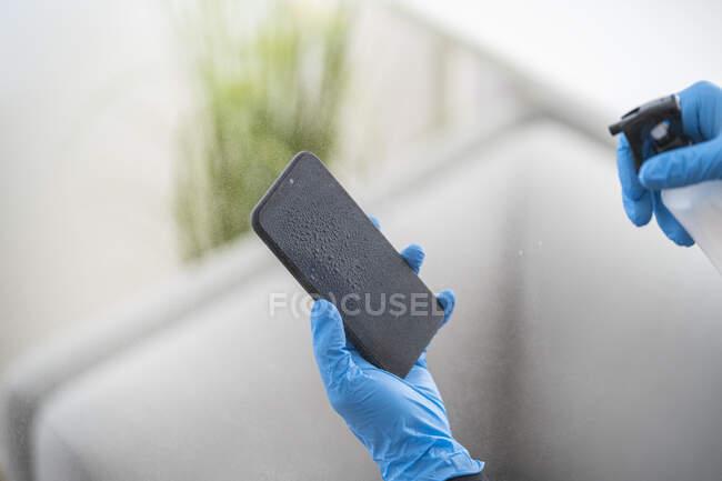 Зблизька жінка дезінфікує мобільний телефон. — стокове фото