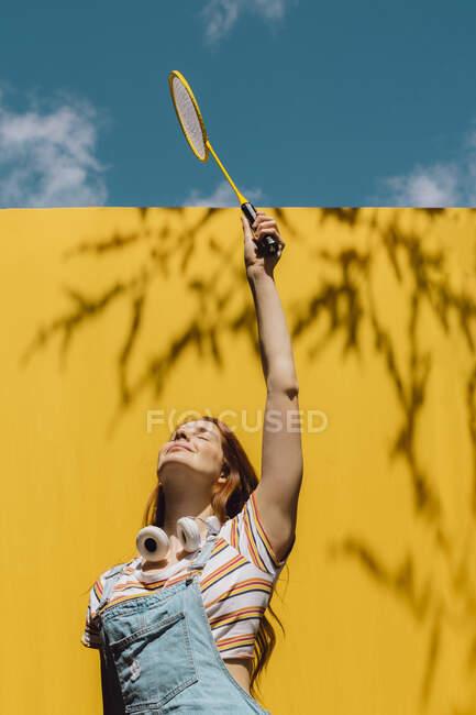 Молодая женщина держит бадминтонную ракетку над желтой стеной в солнечный день — стоковое фото