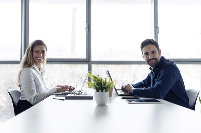 Homme d'affaires et femme assis au bureau, utilisant des ordinateurs portables, souriant à la caméra — Photo de stock