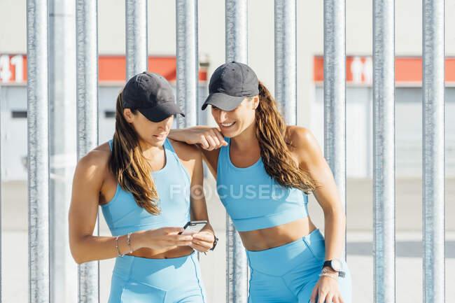 Gemelos jóvenes compartiendo el teléfono inteligente mientras están de pie contra la valla - foto de stock