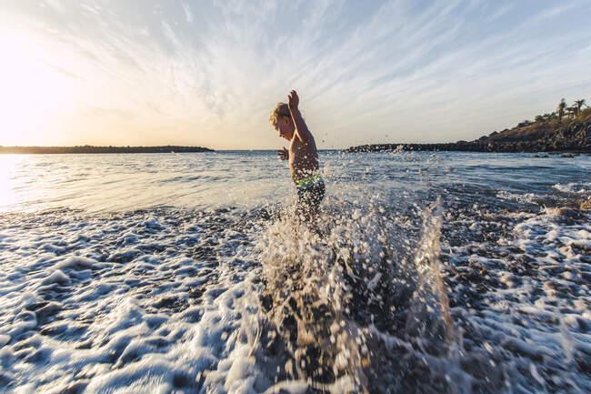 Ragazzo che gioca in acqua sul lungomare, Adeje, Tenerife, Isole Canarie, Spagna — Foto stock