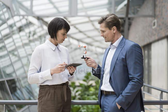 Homme d'affaires et femme debout dans l'atrium de l'immeuble de bureaux, en utilisant une tablette numérique, tenant bras robot — Photo de stock