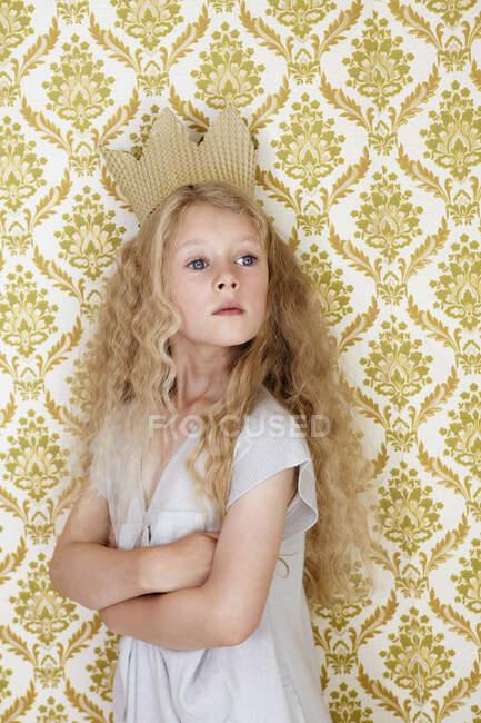 Портрет дівчини, що стоїть біля стіни з картонною короною. — стокове фото