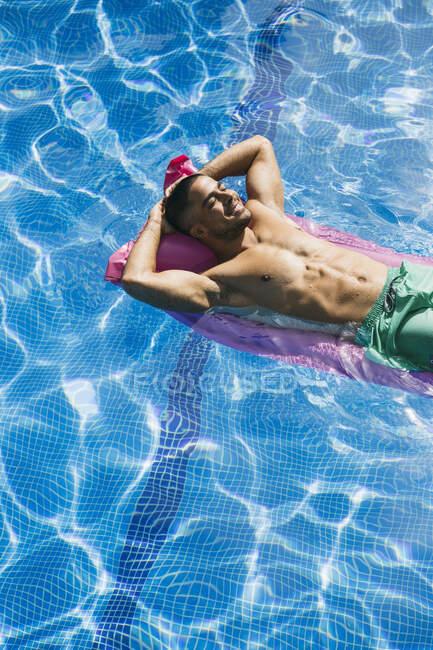 Shirtless bel giovane uomo con le mani dietro la testa rilassante sul letto d'aria in piscina — Foto stock