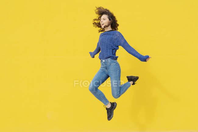 Молода жінка стрибає в повітря перед жовтим фоном. — стокове фото