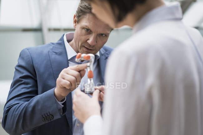 Бізнесмен і жінка стоять у передпокої офісного будинку, розмовляючи про руку робота. — стокове фото