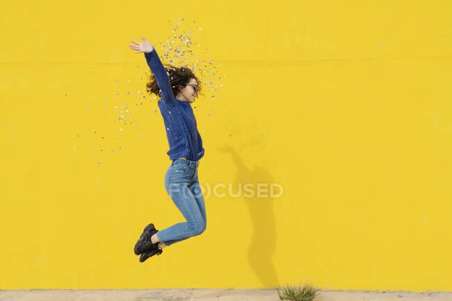 Молода жінка стрибає в повітря перед жовтим фоном, кидаючи конфетті. — стокове фото