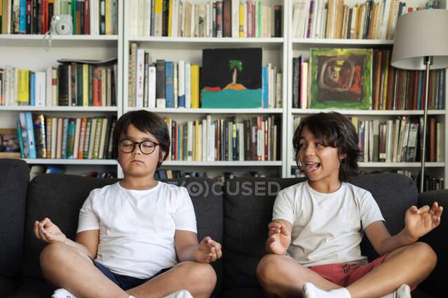 Ragazzo seduto sul divano che medita, suo fratello che lo prende in giro — Foto stock