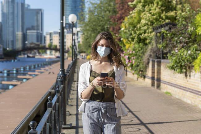Jovem mulher usando máscara protetora andando e usando smartphone — Fotografia de Stock
