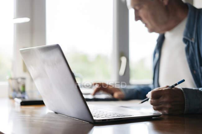 Homem sênior usando calculadora e laptop enquanto escreve em casa — Fotografia de Stock