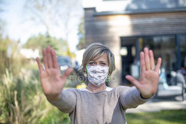 Retrato de una mujer madura que usa mascarilla protectora mientras está de pie con gesto de stop contra casa durante el bloqueo epidémico - foto de stock