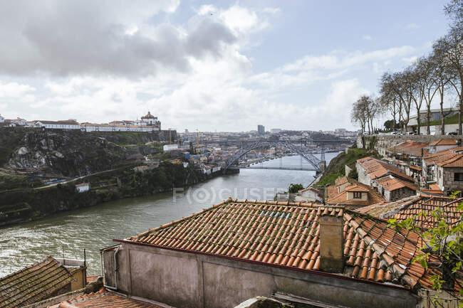 Portogallo, Porto, Case antiche lungo il fiume Douro con il ponte Dom Luis I sullo sfondo — Foto stock