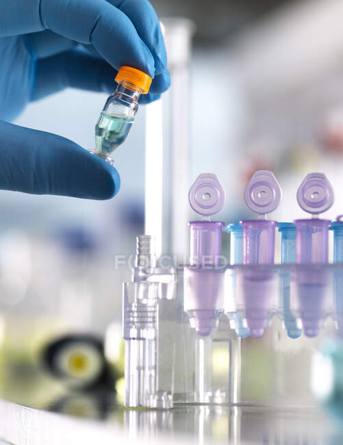 Main coupée du scientifique masculin tenant la formule chimique en flacon au laboratoire — Photo de stock