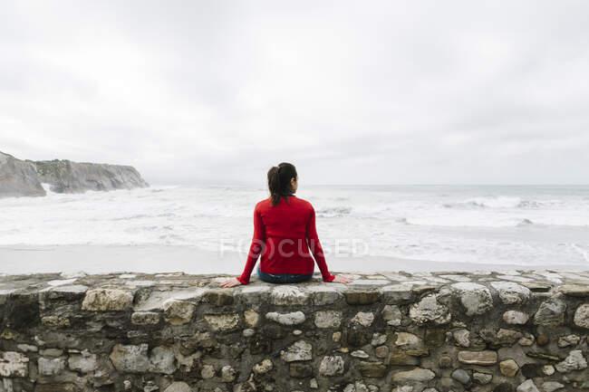 Задній вид спокійної жінки-туристки сидить на стіні, дивлячись на море проти неба, Іцурун, Зумая, Іспанія — стокове фото
