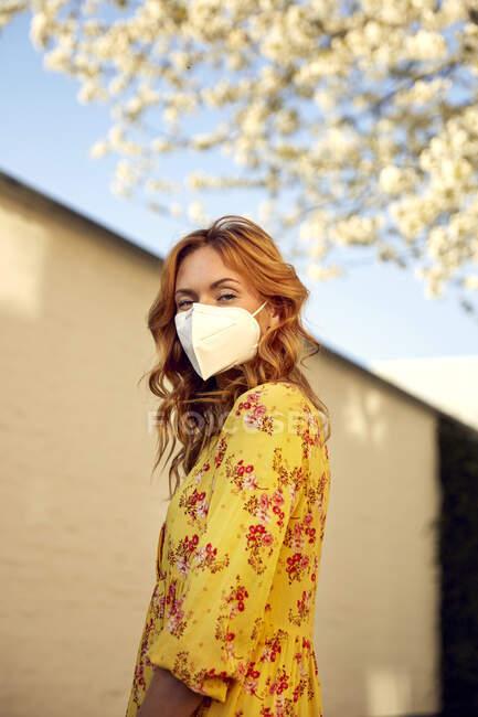 Retrato de una mujer pelirroja con una máscara facial FFP2 en la ciudad - foto de stock