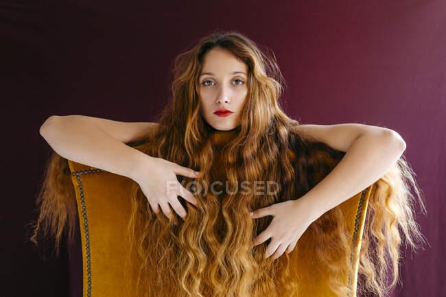 Retrato de mulher jovem confiante com cabelo ondulado marrom longo encostado na cadeira contra fundo colorido — Fotografia de Stock
