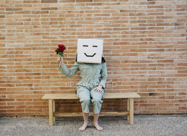 Женщина с красной розой, в картонной коробке со счастливым лицом, сидит на скамейке перед кирпичной стеной — стоковое фото