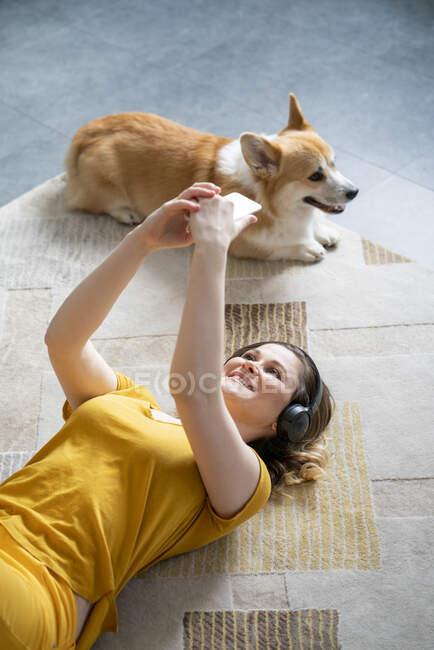Frau mit Hund und Kopfhörer liegt zu Hause mit Smartphone auf dem Boden — Stockfoto