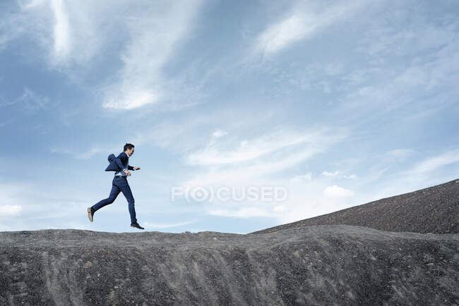 Mature businessman jumping on a disused mine tip — Stock Photo