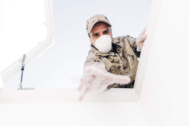 Soldier with face mask on emergency operation, reaching through skylight — Stock Photo